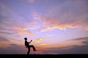 夕陽を背景に元気よく歩く若い男性のシルエットの写真素材 [FYI04616708]