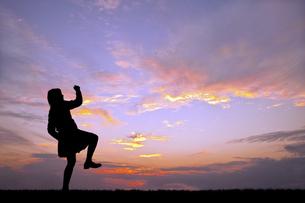 夕陽を背景に元気よく歩く若い女性のシルエットの写真素材 [FYI04616709]
