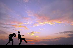 夕陽を背景に元気よく歩く若い男女のシルエットの写真素材 [FYI04616710]