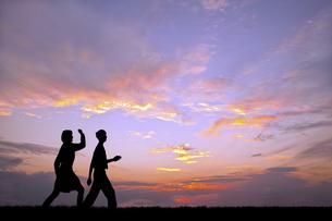 夕陽を背景に元気よく歩く若い男女のシルエットの写真素材 [FYI04616712]
