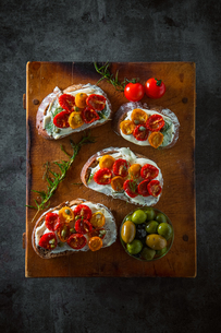 Sliced bread with cream cheese and homemade dried tomatoes on wooden board.Delicious snack.の写真素材 [FYI04620470]