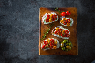 Sliced bread with cream cheese and homemade dried tomatoes on wooden board.Delicious snack.の写真素材 [FYI04620471]