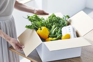 ダンボールから野菜を取り出す女性の写真素材 [FYI04620664]