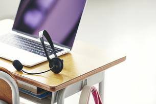 勉強机に置かれたノートPCとヘッドセットの写真素材 [FYI04621172]