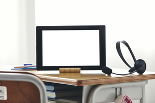 勉強机に置かれたタブレットPCとヘッドセットの写真素材 [FYI04621179]