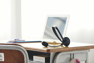 勉強机に置かれたタブレットPCとヘッドセットの写真素材 [FYI04621180]