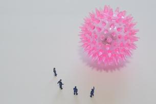 巨大なコロナウイルスを監視する警察官のミニチュア人形の写真素材 [FYI04621254]