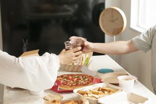 テイクアウトのランチを前に乾杯するカップルの手元の写真素材 [FYI04622207]