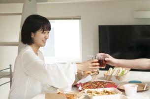テイクアウトのランチを前に乾杯するカップルの写真素材 [FYI04622208]