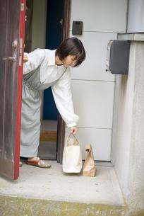 玄関に置かれたデリバリーを受け取る若い女性の写真素材 [FYI04622211]