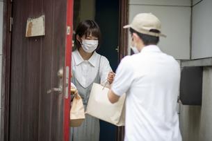 玄関で紙袋を手渡される若い女性の写真素材 [FYI04622217]