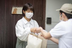 玄関で紙袋を手渡される若い女性の写真素材 [FYI04622218]