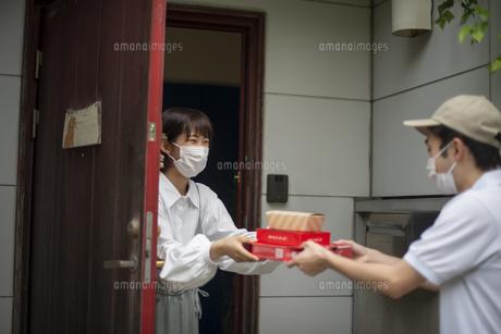 玄関でデリバリーを受け取る女性の写真素材 [FYI04622223]