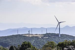 霞む山並みを見る丘の上に立つ風力発電風車の写真素材 [FYI04623498]