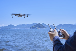ドローンを操縦する日本人男性の手元の写真素材 [FYI04623876]