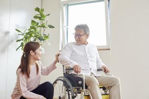 車椅子のシニアの男性を介助する若い女性の写真素材 [FYI04623886]