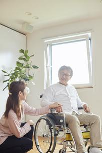 車椅子のシニアの男性を介助する若い女性の写真素材 [FYI04623893]