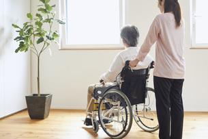 車椅子のシニアの男性を介助する若い女性の写真素材 [FYI04623901]