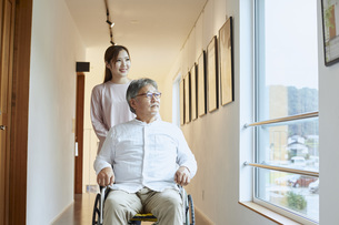 車椅子のシニアの男性を介助する若い女性の写真素材 [FYI04623911]