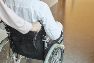 車椅子のシニアの男性を介助する若い女性の写真素材 [FYI04623914]