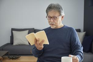 部屋の中で読書をするシニアの男性の写真素材 [FYI04623932]