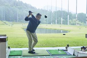 ゴルフ場で練習をするシニアの男性の写真素材 [FYI04623963]