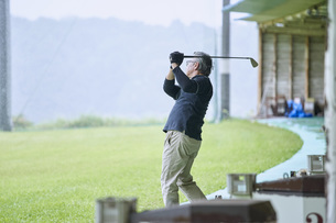 ゴルフ場で練習をするシニアの男性の写真素材 [FYI04623965]