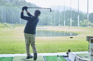 ゴルフ場で練習をするシニアの男性の写真素材 [FYI04623966]