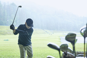 ゴルフ場で練習をするシニアの男性の写真素材 [FYI04623967]