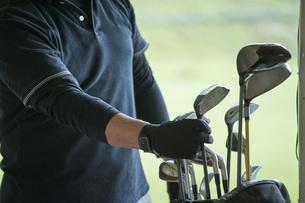 ゴルフ場で練習をするシニアの男性の手元の写真素材 [FYI04623969]