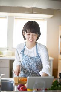 キッチンで料理をする若い女性の写真素材 [FYI04624099]