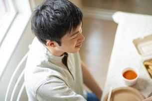 食事をする若い男性の写真素材 [FYI04624101]