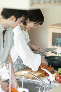 キッチンで料理をするカップルの写真素材 [FYI04624114]