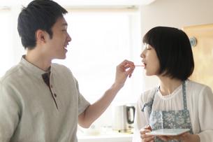 キッチンでつまみ食いをするカップルの写真素材 [FYI04624128]