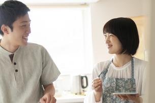 キッチンで笑い合うカップルの写真素材 [FYI04624129]