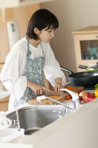 キッチンで人参を切る若い女性の写真素材 [FYI04624133]