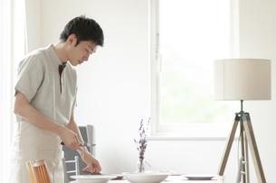 食事の準備をする若い男性の写真素材 [FYI04624136]