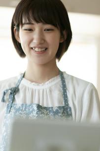 タブレットPCを見ながら料理をする若い女性の写真素材 [FYI04624145]