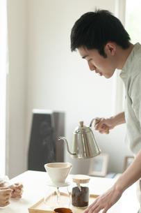 リビングでコーヒーを淹れる男性の写真素材 [FYI04624152]