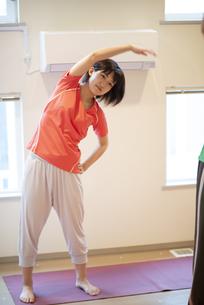 自宅で体操をする若い女性の写真素材 [FYI04624158]