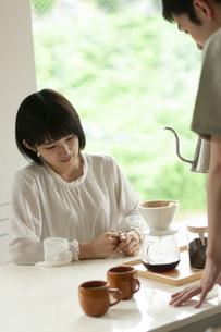 コーヒーを淹れてもらう女性の写真素材 [FYI04624159]