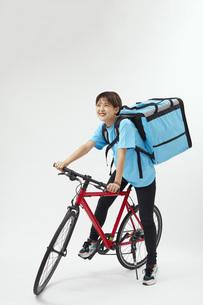 自転車でフードデリバリーを行う女性の写真素材 [FYI04624597]