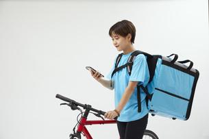 自転車でフードデリバリーを行う女性の写真素材 [FYI04624598]