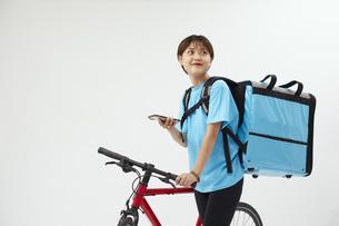 自転車でフードデリバリーを行う女性の写真素材 [FYI04624599]