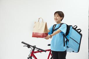 自転車でフードデリバリーを行う女性の写真素材 [FYI04624600]