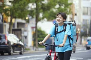 自転車でフードデリバリーを行う女性の写真素材 [FYI04624602]