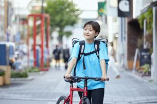 自転車でフードデリバリーを行う女性の写真素材 [FYI04624604]