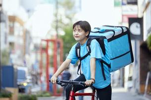 自転車でフードデリバリーを行う女性の写真素材 [FYI04624605]
