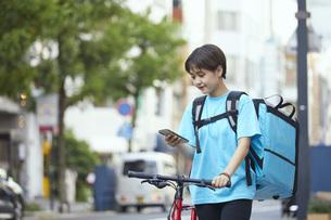自転車でフードデリバリーを行う女性の写真素材 [FYI04624606]