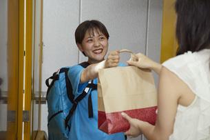 フードデリバリーを行う若い女性の写真素材 [FYI04624607]